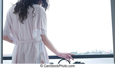 sexy girl in pink silk robe stands on the balcony and dances...
