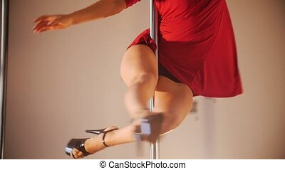 Sexy girl in red dress pole dance. Spinning around the pole. Legs shown.