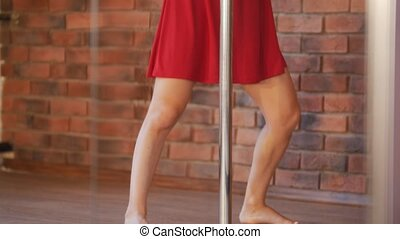 Sexy girl in red dress prepares to training her pole dance....