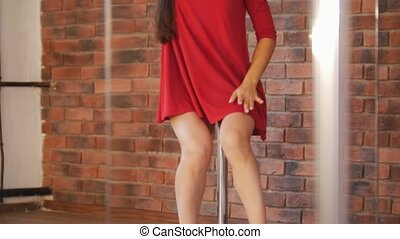 Sexy girl in red dress training pole dancing in studio.