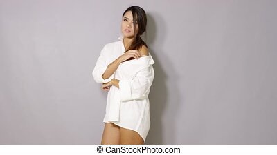 Sexy girl in white mens shirt posing on gray