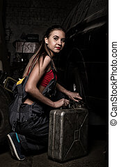 sexy girl mechanic sitting next to the machine and holding a can of gasoline. colorless life concept