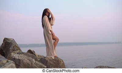 Sexy girl model stands on stones against the sea in a long dress. slow motion. 4K