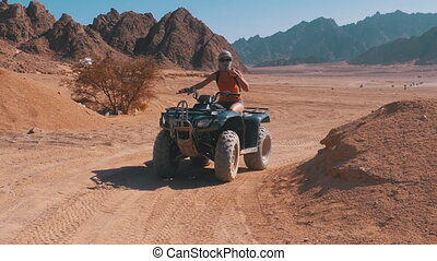 Sexy Girl on a Quad Bike Rides through the Desert of Egypt on Background of Mountains. Driving ATVs. Adventures of desert off-road on ATVs. Safari excursion. Woman in keffiyeh is riding an ATV in Sharm el Sheikh. Travel, vacation, and active lifestyle.