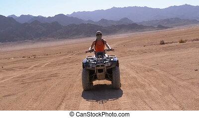 Sexy Girl on a Quad Bike Rides through the Desert of Egypt...