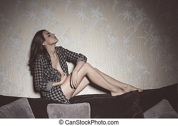 sexy girl on backrest of sofa - cute brunette woman with...