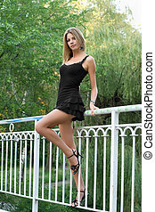 Sexy girl on railing of the bridge