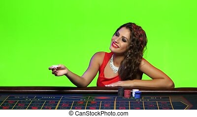 Sexy girl plays with chip sitting at the poker table