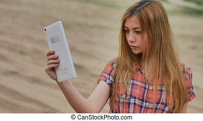 sexy girl selfie with the tablet on the sand in desert slow motion outdoors