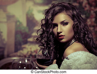 Sexy girl sit with wine in fur coat at evening look at...
