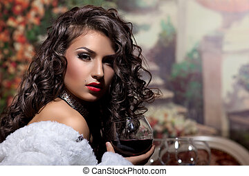 Sexy girl sit with wine in fur coat at evening