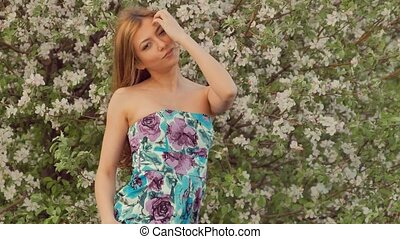 sexy girl smiles near a blossoming apple tree