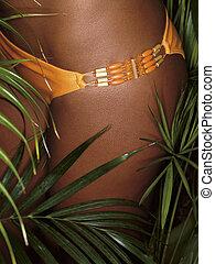 photo of girl thighs in orange bikini with tropical plants