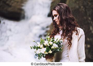 Sexy girl with a wedding bouquet of flowers against the background of a glacier and mountains