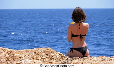 Sexy Girl with Exotic Cocktail Sitting on a Beach against the Sea