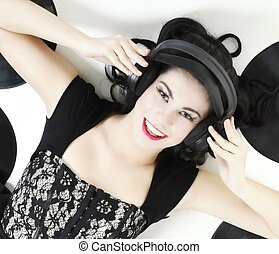 Sexy happy girl with phonography analogue record and headphones music lover retro style studio shot