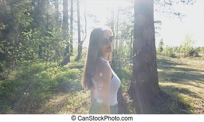 Sexy girl with red lips walks in sunglasses on a sunny summer day in the woods.