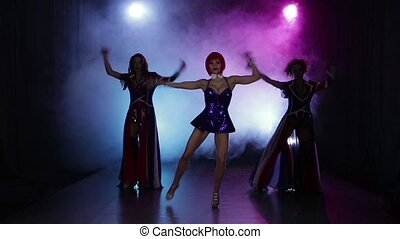 Sexy girls dance in small night club. Smoky multicolored background