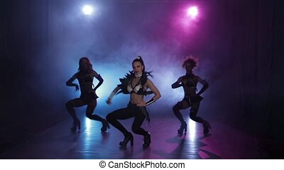 Sexy girls dancing in original leather outfit in lights. Smoky