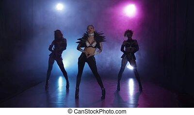 Sexy girls dancing in original outfit in lights. Smoky studio