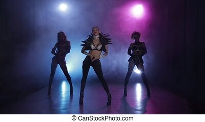 Sexy girls dancing in original outfit in lights. Smoky studio
