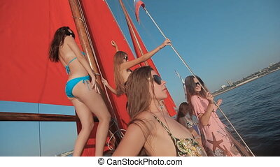 Sexy girls in bikini dancing on a yacht with red sails and a Russian flag