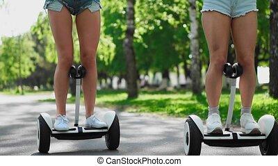 Sexy girls in short denim shorts ride on white Segways close...