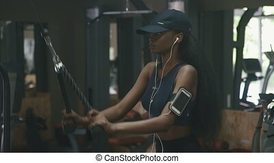 Sexy gorgeous african-american woman working out at the gym and listens to music in white earphones