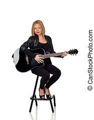Sexy guitarist sitting with a black leather jacket isolated...