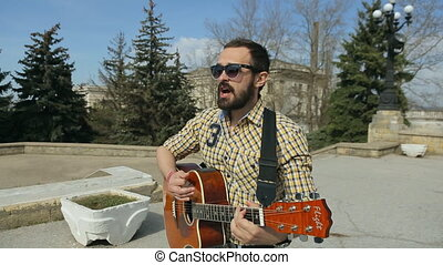 Sexy guy with a beard in glasses playing guitar on the street