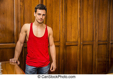 Sexy handsome young man standing against wardrobe