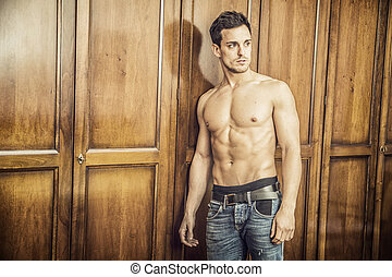 Sexy handsome young man standing shirtless against wardrobe