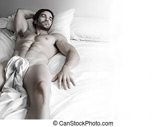 Sexy hunk in bed - Beautiful young nude muscular male model...