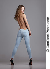 Sexy jeans - Young topless lady in blue jeans on gray...