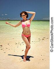 sexy, junge frau, mit, sonnenbrille, besitz, sie, dunkles haar, posierend, als, ob, tanzen, auf, feiner sand, sandstrand, mit, gelassen, klar, meer, in, hintergrund., watamu, kenia