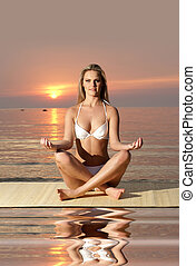 Sexy lady wearing swimsuit - Sexy lady meditating on the...