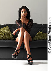 Sexy leggy woman in heels on black leather sofa - Young...