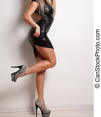 Sexy legs of woman with leather dress and high heels