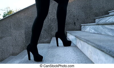 Sexy legs with high black heels climbs stairs of city....