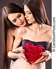 Sexy lesbian women taking heart in erotic foreplay game.