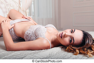 Sexy lovely young woman in lingerie lying on bed