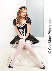 Sexy maid. Beautiful young maid in white pantyhose sitting...
