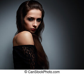 Sexy makeup brunette woman with long hair looking on dark shadow background