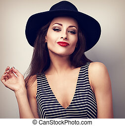 Sexy makeup woman in black fashion hat and bright red lipstick posing