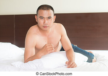 Sexy male model in bed at home alone