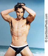 Sexy male model in fashion swimwear posing