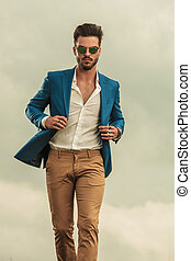 sexy man holding blue suit walking on clouds background