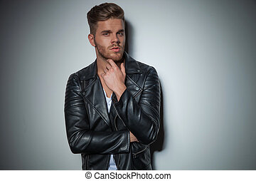 sexy man in black leather jacket is thinking