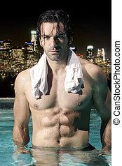 Sexy man in pool at night