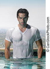 Fashion portrait of a gorgeous male model in soaked wet t-shirt standing in luxurious swimming pool with city background